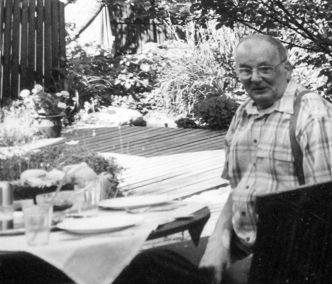 Anin isä mustavalkoisessa kuvassa puutarhassa.